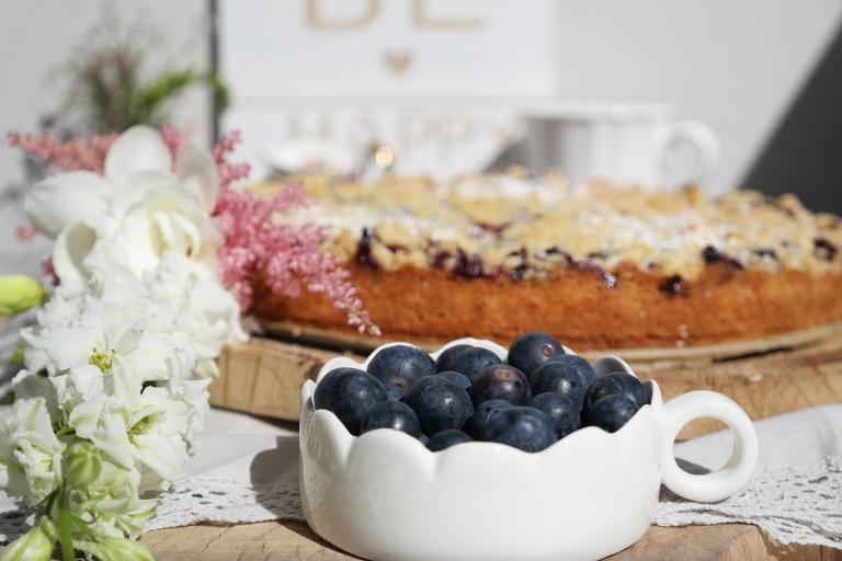Schale mit Heidelbeeren und Kuchen im Hintergrund
